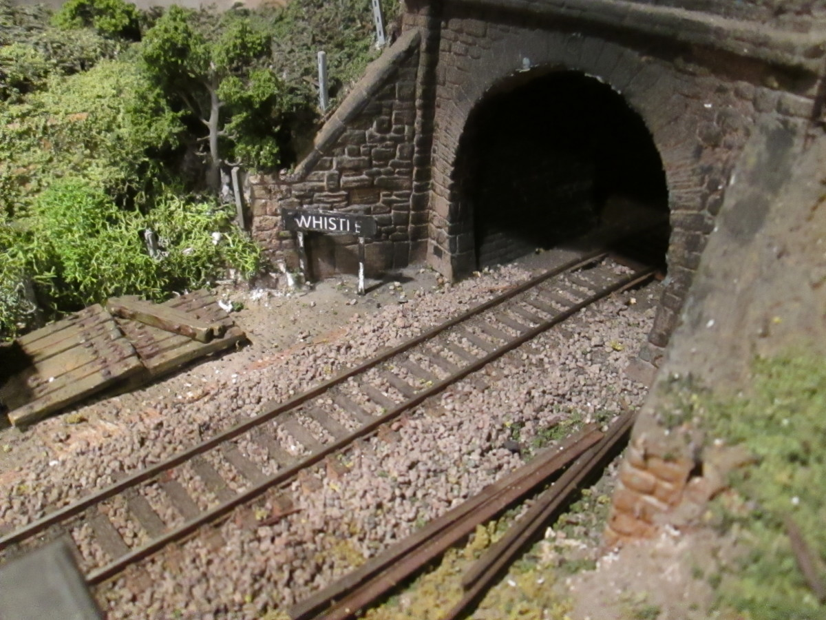 The 'boxed' tunnel mouth on the Ayton Row side of the main 'tunnel', ballasted track, rusted rails at the trackside, 'whistle' board, sleeper stack, fence posts and vegetation aplenty. Tunnel mouth blacked within to reinforce effect