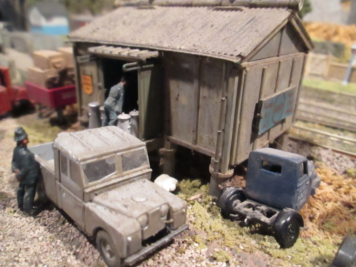 Ayton Row's provender store (Ratio) with ballast road, metal kit-built 'mechanical horse' in LNER blue livery, Oxford 4mm Land Rover pick-up, white metal painted figures, plastic milk churns from Peco'