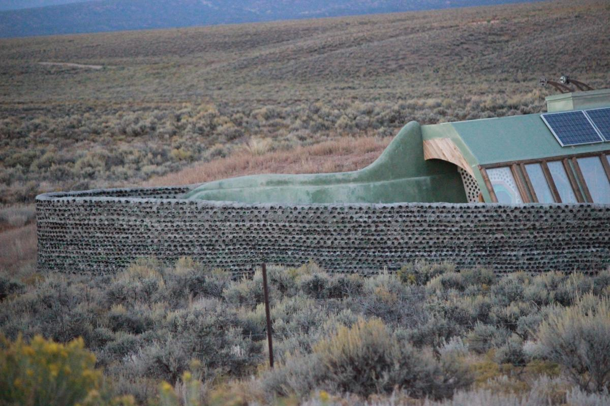 Earthship near Taos, New Mexico.  A cement privacy fence, made with recycled bottles.