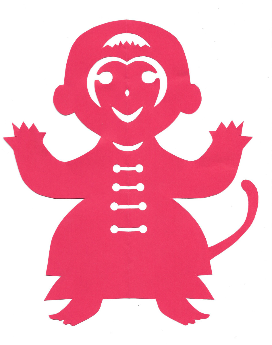 A papercut of a monkey in a little jacket done Chinese style in the lucky color red.