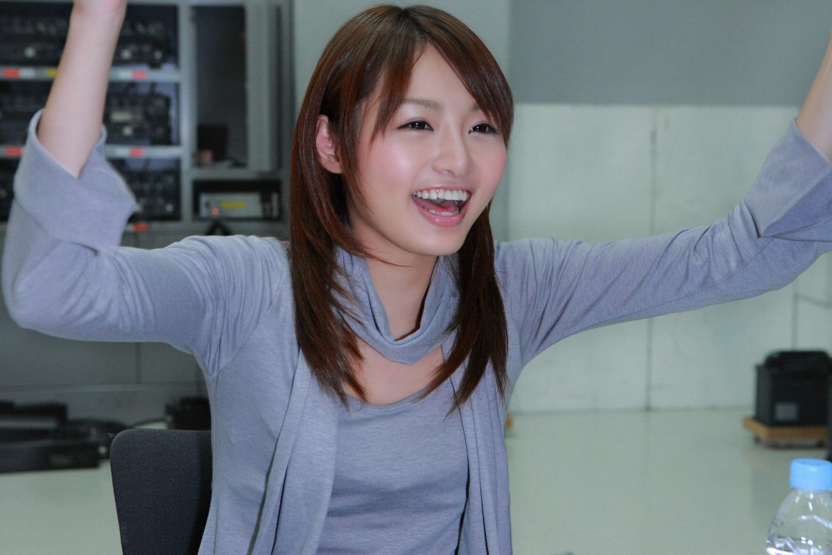Saori Yoshikawa throws her arms up in the air in celebration about something.