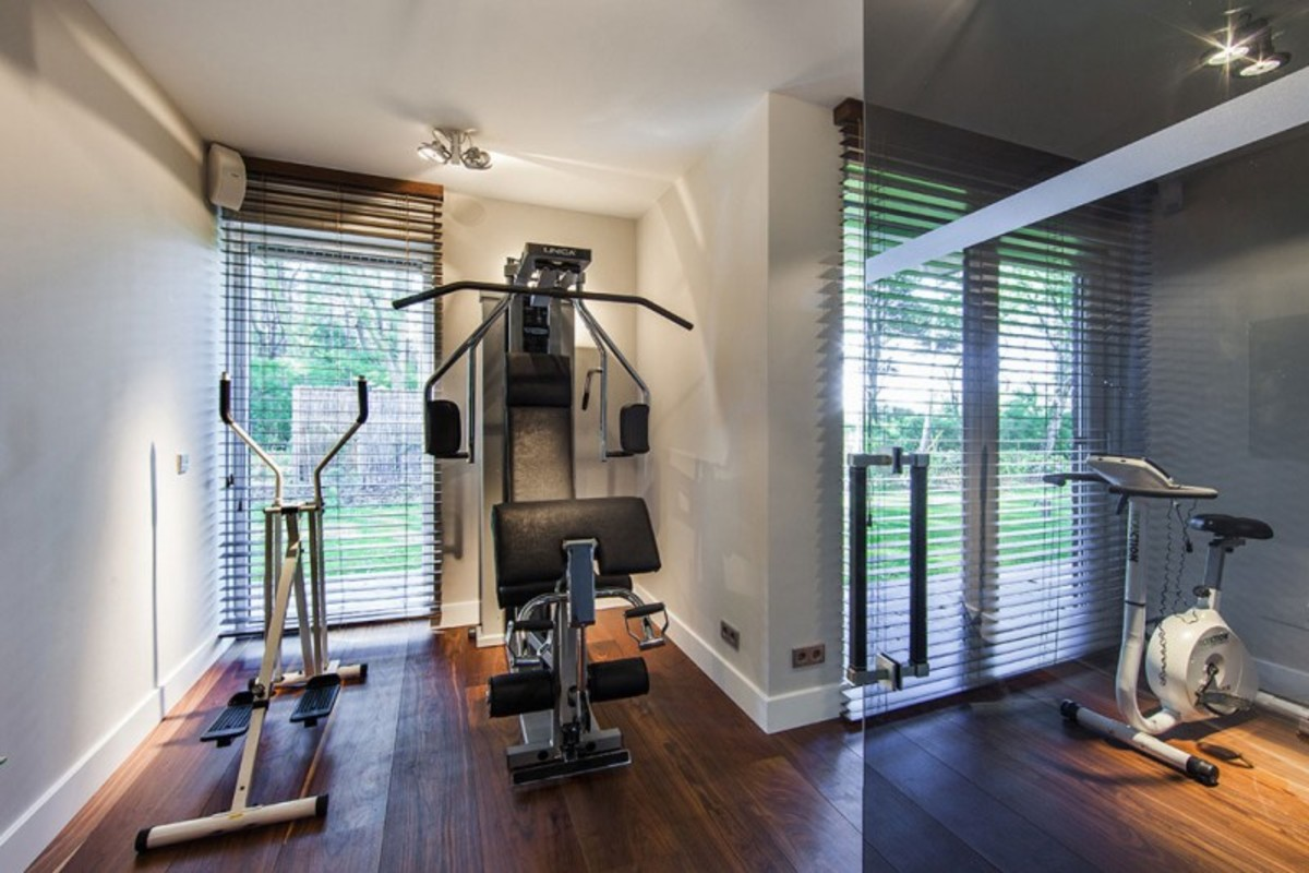 Wood Blinds and a Wood Floor in a Home Fitness Room Provide an Inviting Home Decor