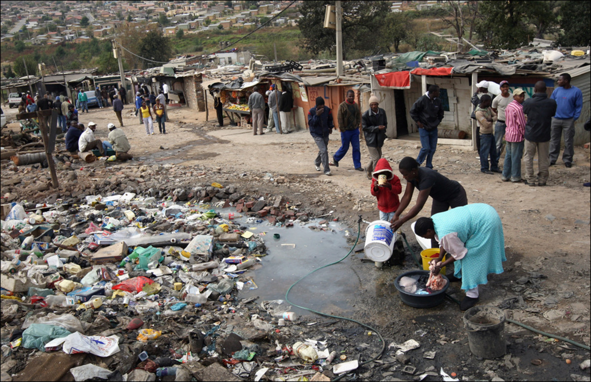 Squatter Camp Near Alexander Township In Johannesburg, and its inhabitants using a public water tap for everything