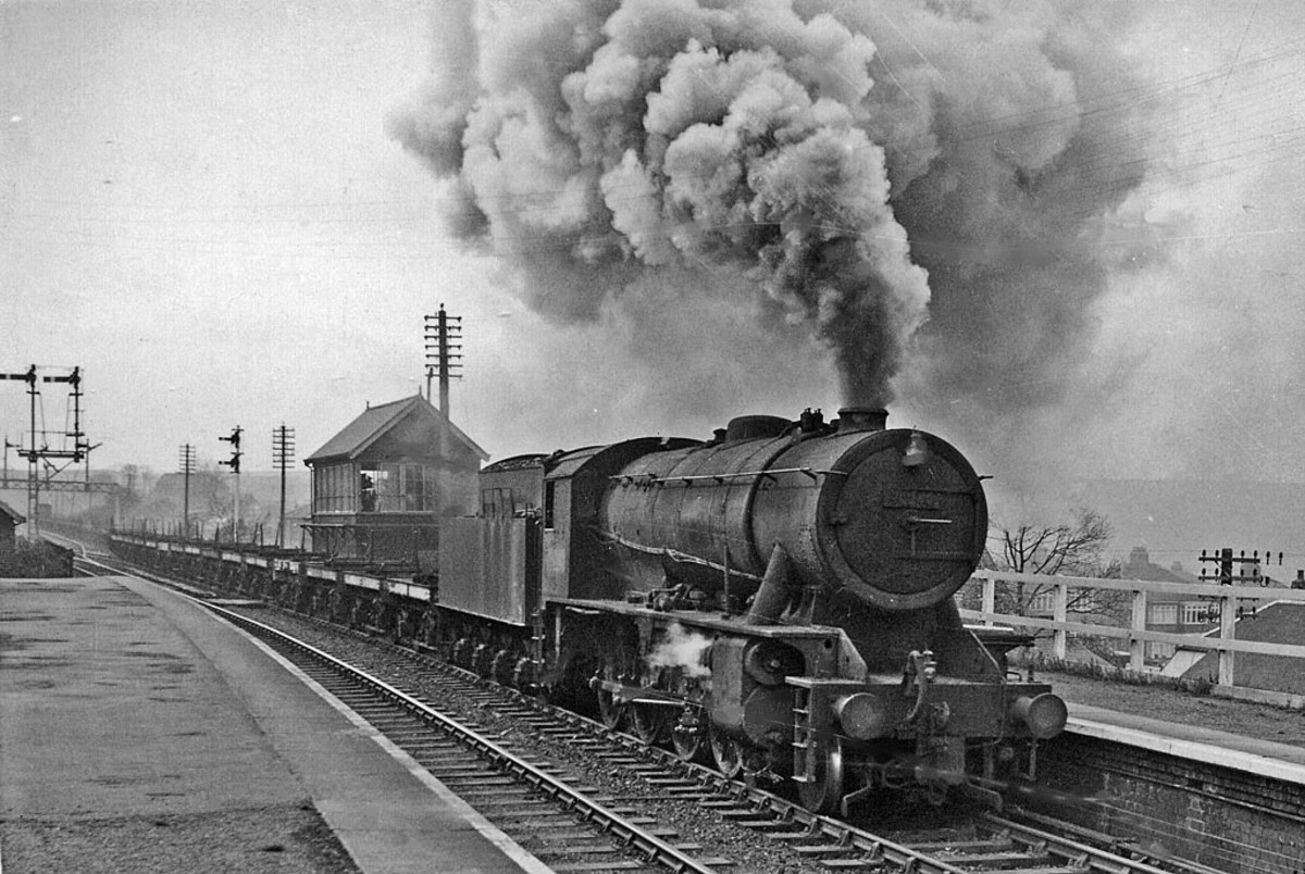 At the easternmost end of the Cleveland Railway, unidentified Riddles' War Department 2-8-0 with empty bolster wagons heads to Skinningrove Works for coil load. The brake van can be seen at the left below the bracket signal and gantry beyond