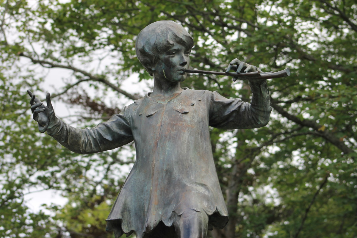 Peter Pan playing his flute from his position atop the statue.