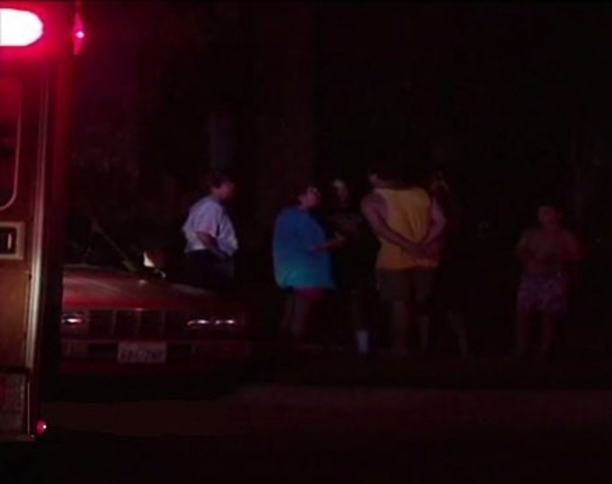 Curious neighbors from Eagle Drive gather in front of the Routier home the night of the murders.