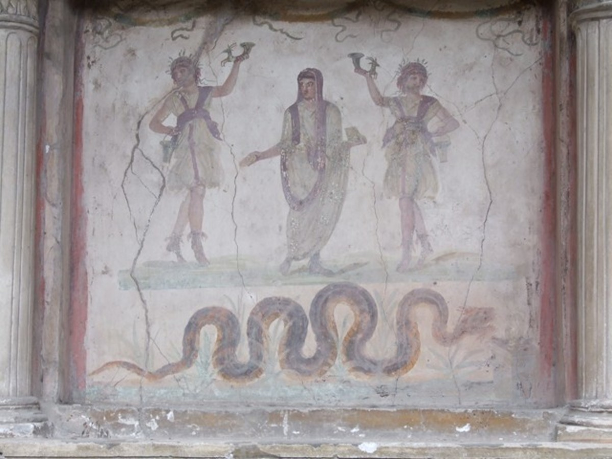 VI.15.1 Pompeii. December 2006. Household lararium in service area. Painting of serpent, (Agathodemone), garlands and three figures. The household gods (Lares) are either side of the guardian spirit (genius loci) of the house.