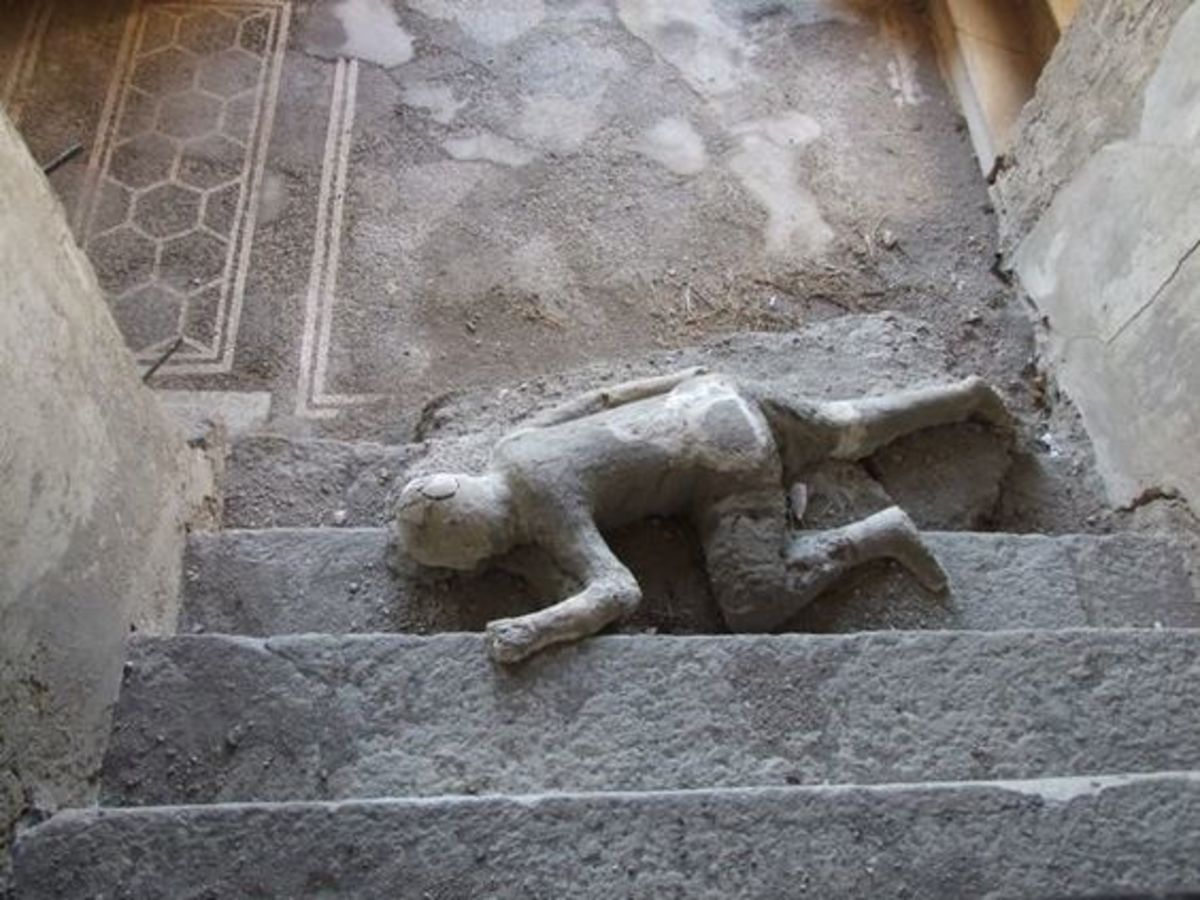 VII.16.17-22 Pompeii. December 2007. Plaster cast of body lying at foot of staircase. Four people met their death in this house, three of them died huddled together on this staircase. Cases were made from their skeletal remains