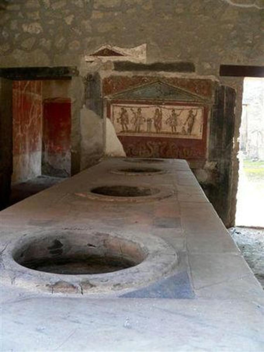A thermopolium was the equivalent of a modern day cafe/bar. Hot and cold food was sold from what was usually an 'L' shaped masonry counter containing terracotta vessels.  ©Jackie and Bob Dunn