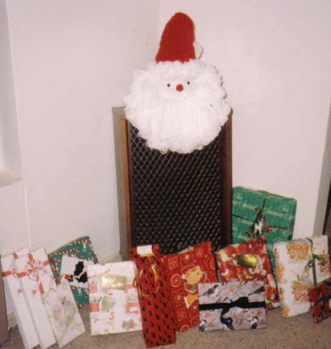 Here the Santa face perches on a stereo speaker. Surrounded by gifts, it takes the place of a Christmas tree in an apartment that is short on space.