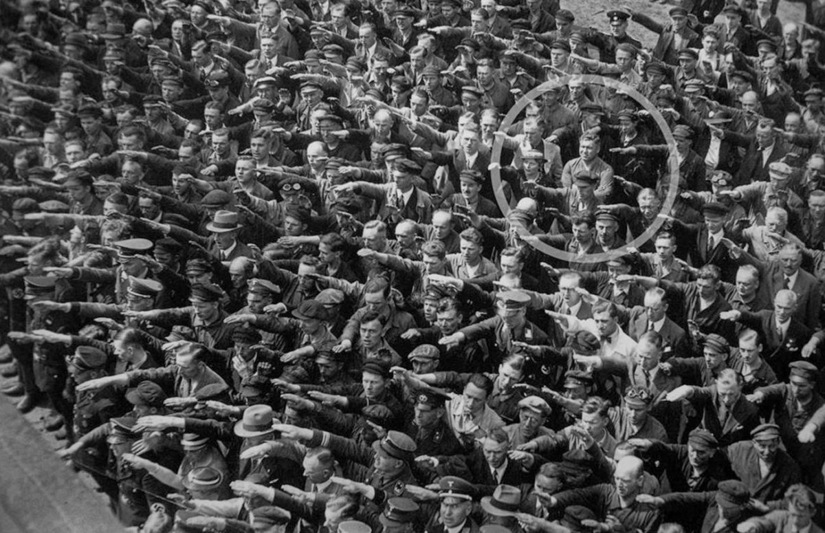 The man who didn't salute Hitler. A German man standing at a rally in 1936. Hamburg, refuses to give the Nazi salute. The photo laid unnoticed for nearly 55 years