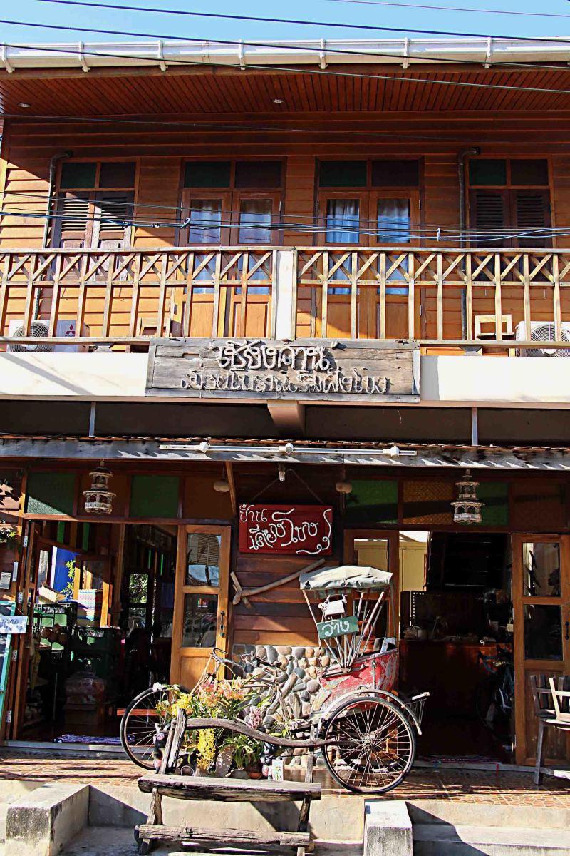 An original teakwood building, with a rickshaw in front - a sign of Chiang Khan catering to the tourist invasion