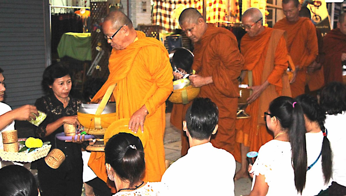 Alms giving - Before dawn, monks process along a line of devotees