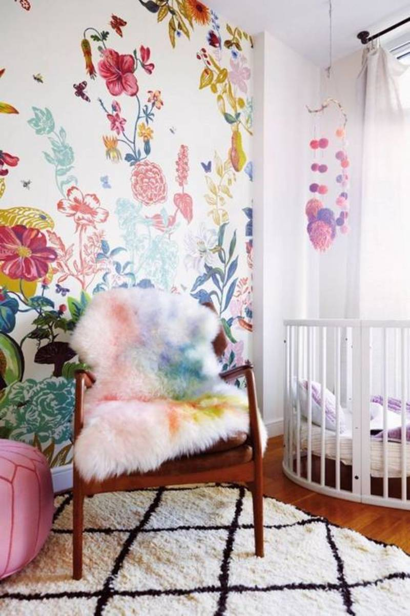 The bright colors inspire the accessories with the watercolor sheepskin & pom-pom mobile over the crib.