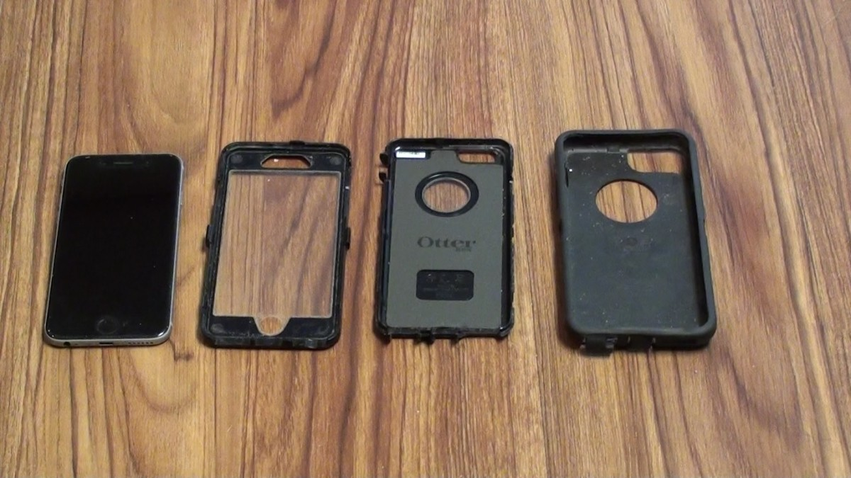 The three pieces of the OtterBox Defender case setting next to an iPhone 6.