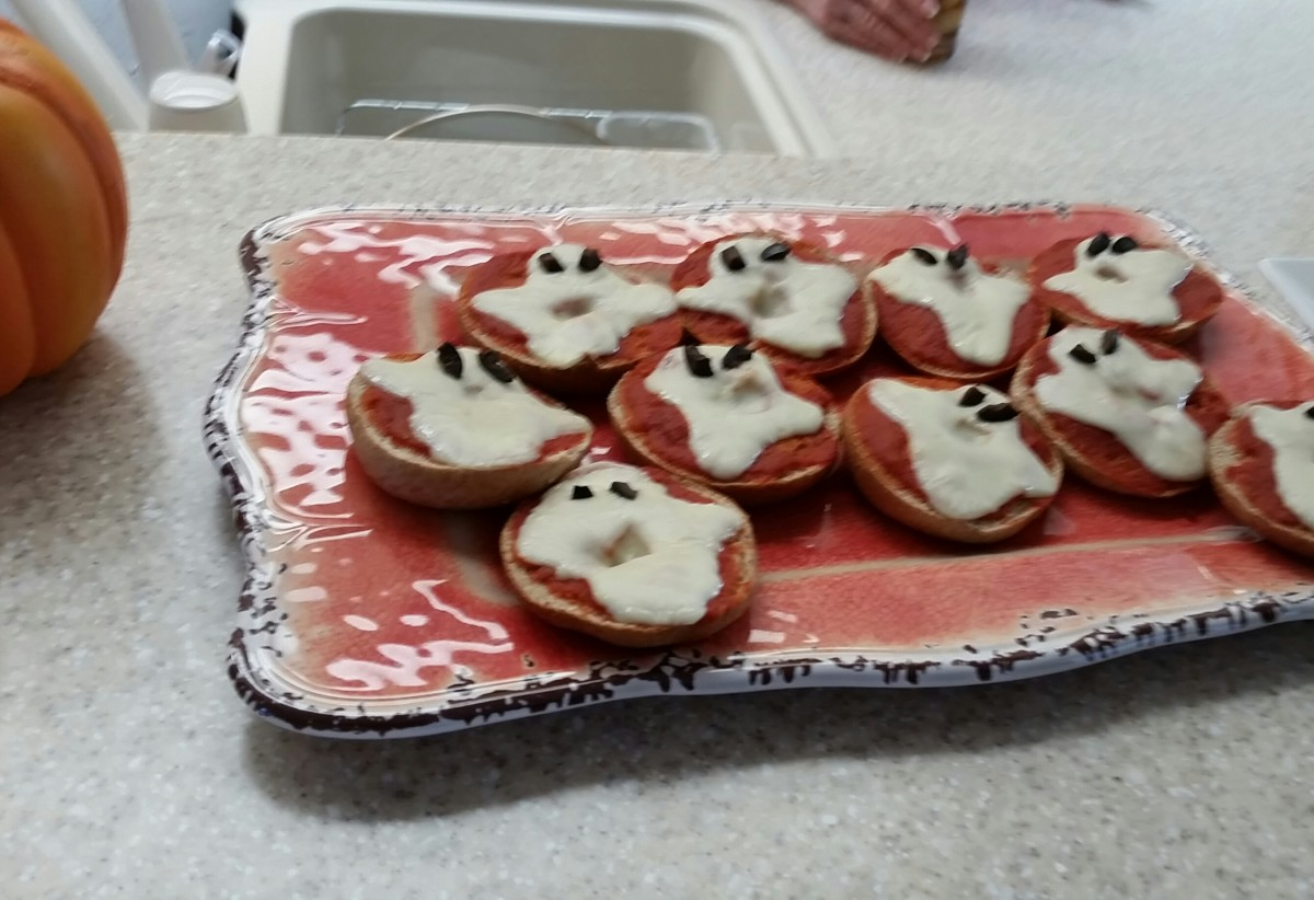 Get the miniature bagels, spread pizza sauce on them. Remove bits from mozzarella cheese to form ghost shapes. Heat until the cheese melts. Small bits of black olives can serve as eyes.