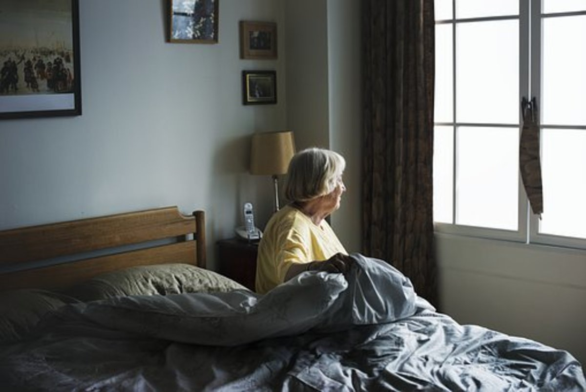 Elderly women getting out of bed