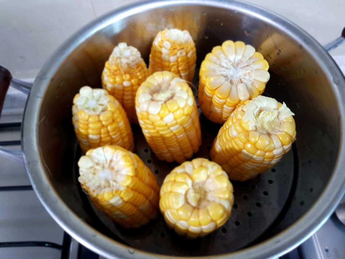 To steam sweet corn, cut them into half and stack them vertically in the steamer tray