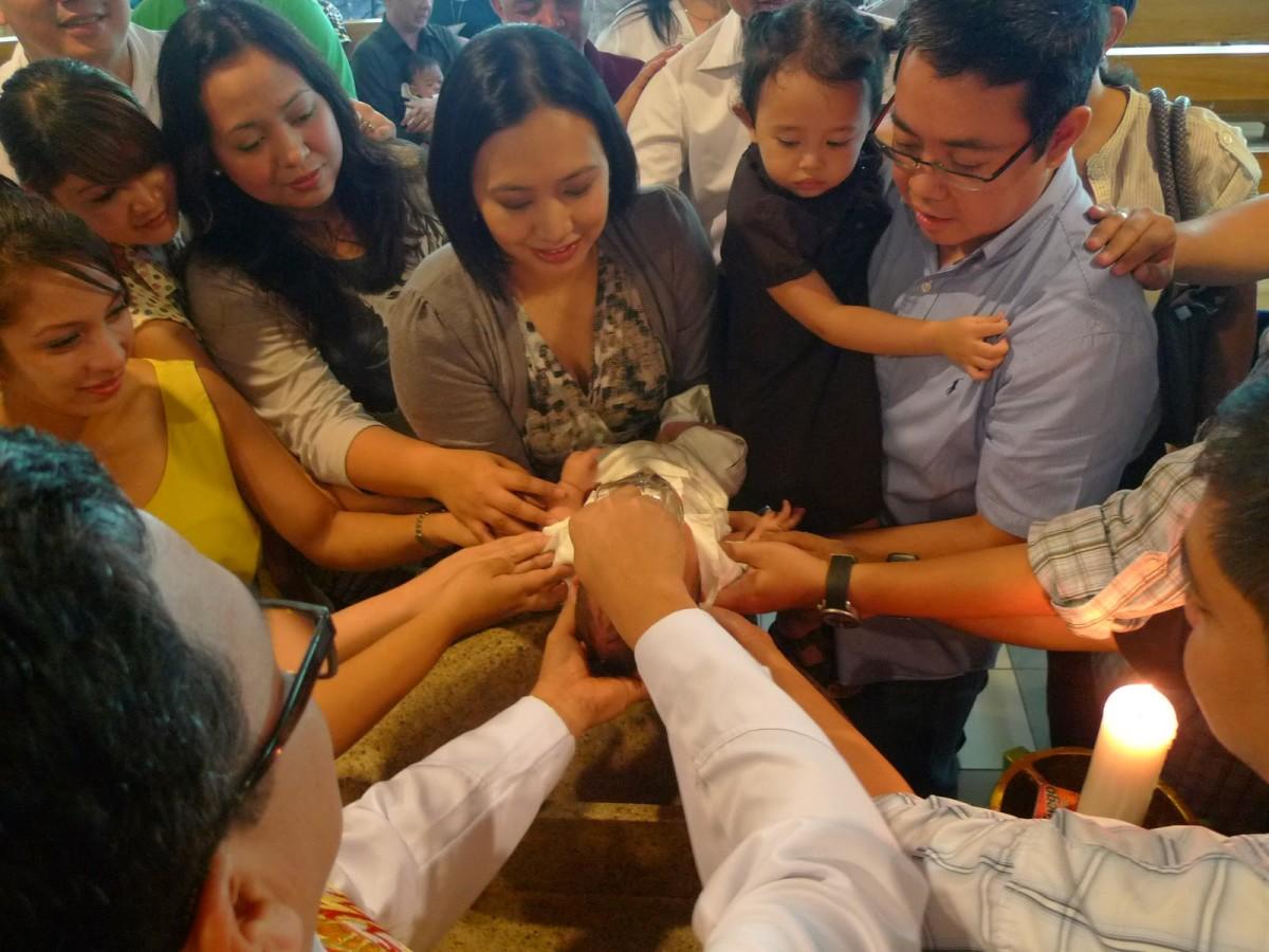 A baptismal with the parents and the baby's ninong and ninang.