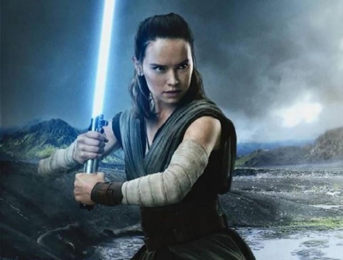 Rey with Luke's lightsaber