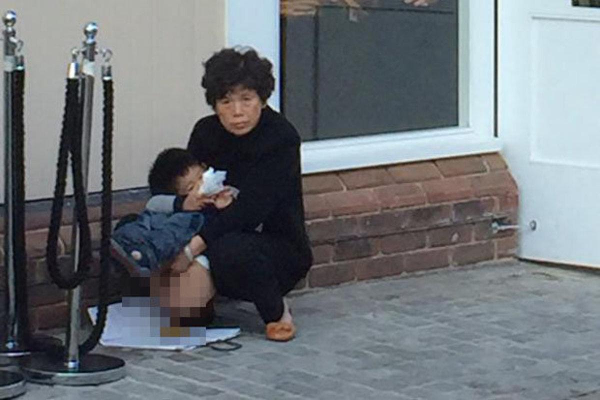 A woman letting her kid soil public places.