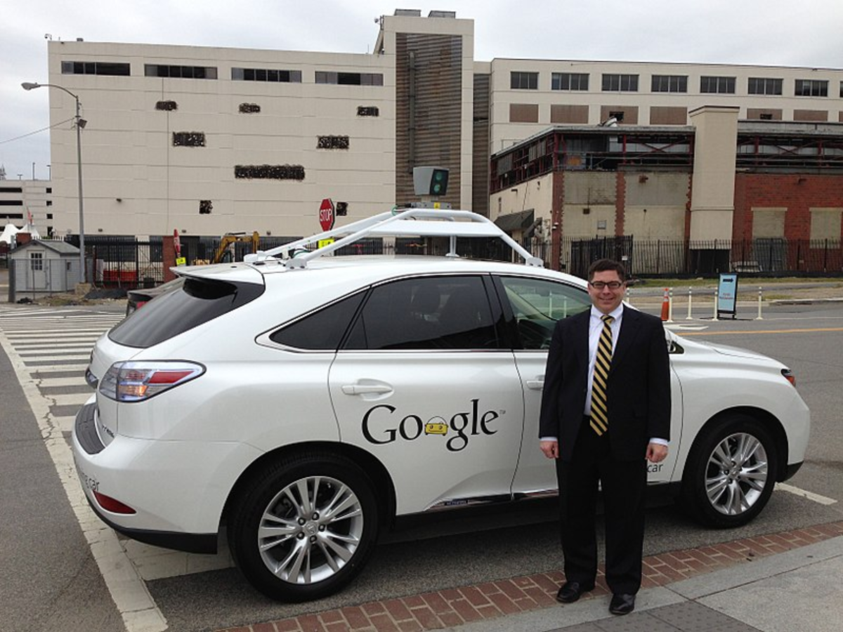 FCC Commissioner Michael O'Rielly standing next to Google's self-driving car ( April 28, 2014); now Waymo (Alphabet), began as the Google Self-Driving Car Project in 2009.