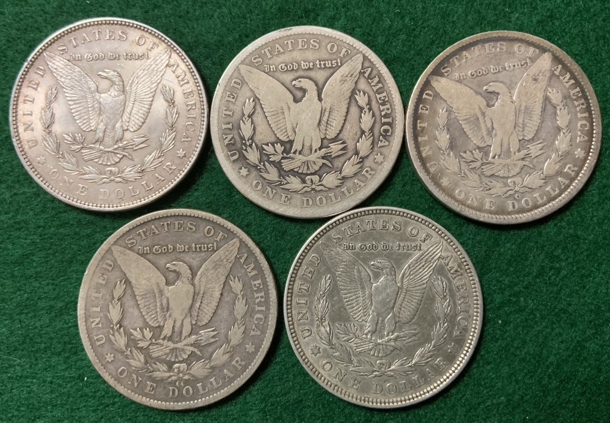 Five mint marks of the Morgan dollar below eagle. Upper-left: no mint mark for Philadelphia. Middle-top: S for San Francisco. Top-right: O for New Orleans. Bottom-left: CC for Carson City. Bottom-right: D for Denver (note how small it is).