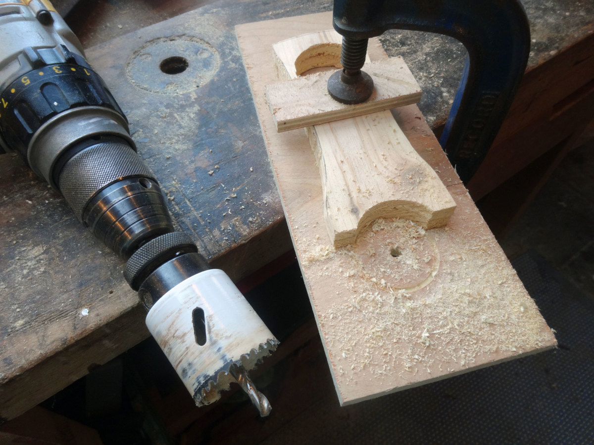 Using sacrificial wood for grip for the drill bit, so as to use a hole cutter saw for creating the curved base of the stand.