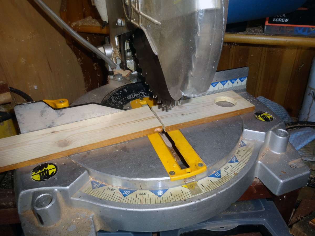 Using a mitre saw to cut the wood to the desired length.