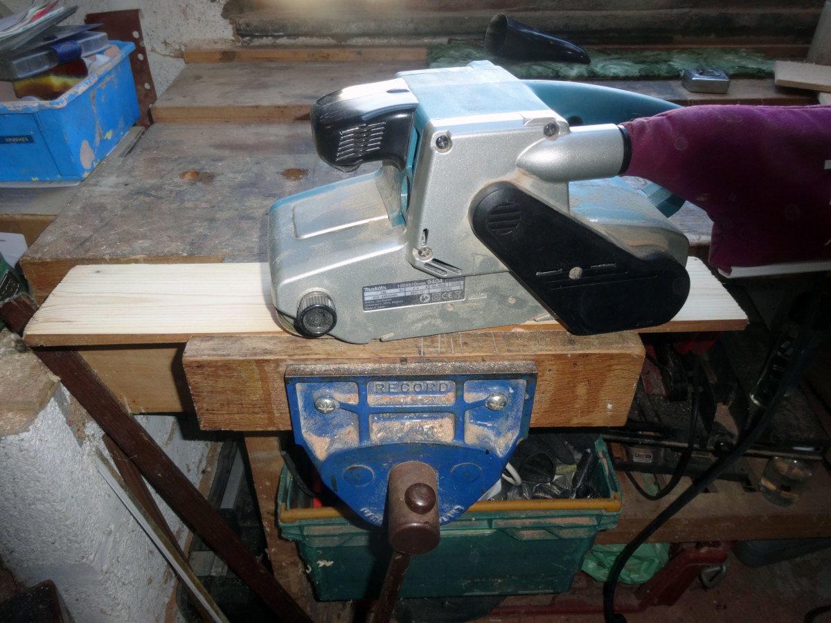 Using the belt sander to get back to the bare wood, and give a smooth surface.