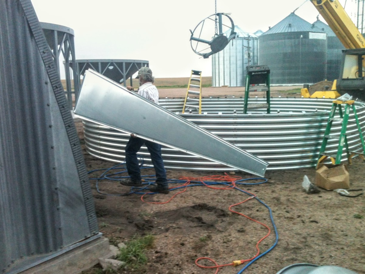 Roof sheets are brought in one at a time, and distributed around the perimeter of the first ring, until there are four ready.