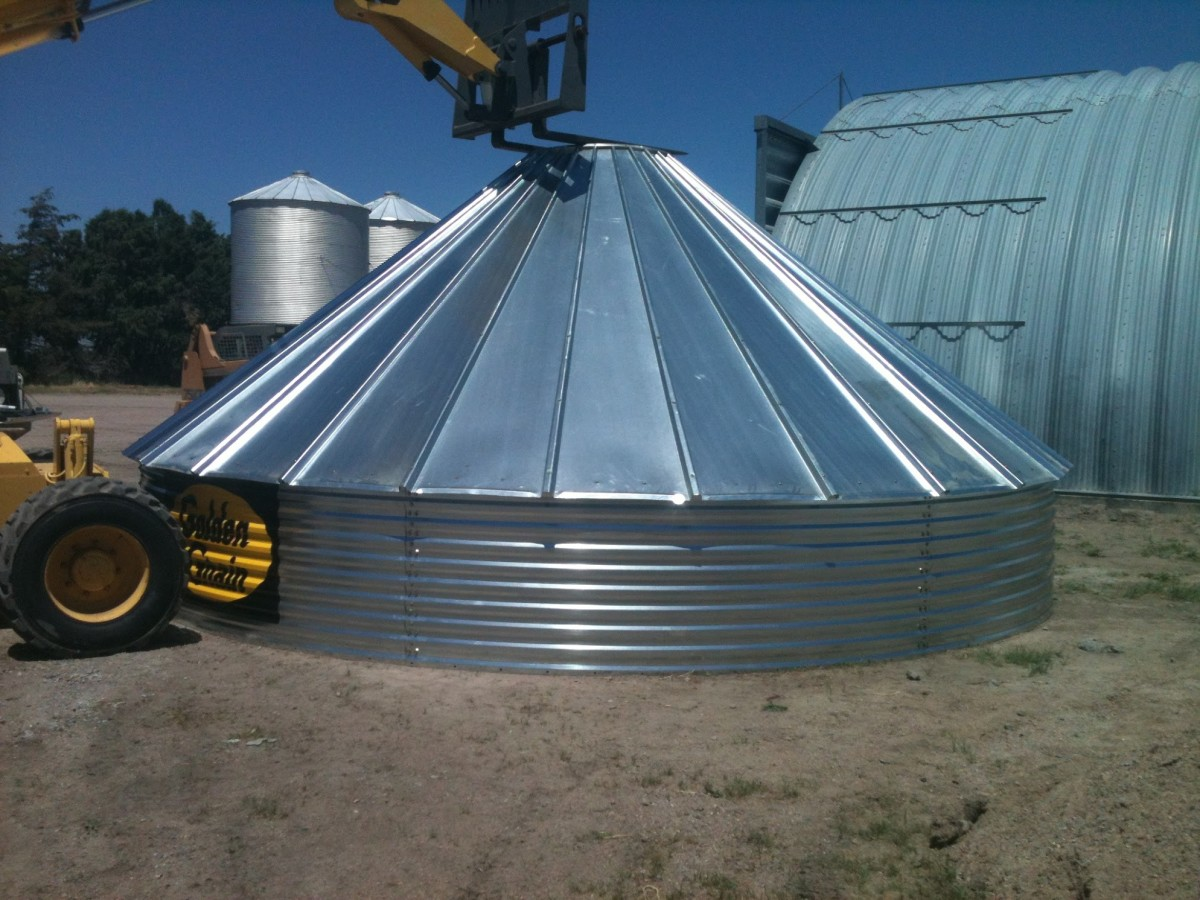 A finished roof and first ring await further developments. The bin is held down at the peak with the forks of a large forklift.