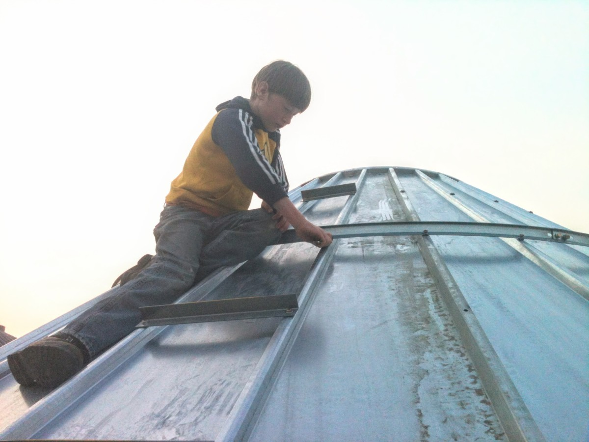 A person with a box-end wrench assists on the outside of the roof to hold the bolts still.