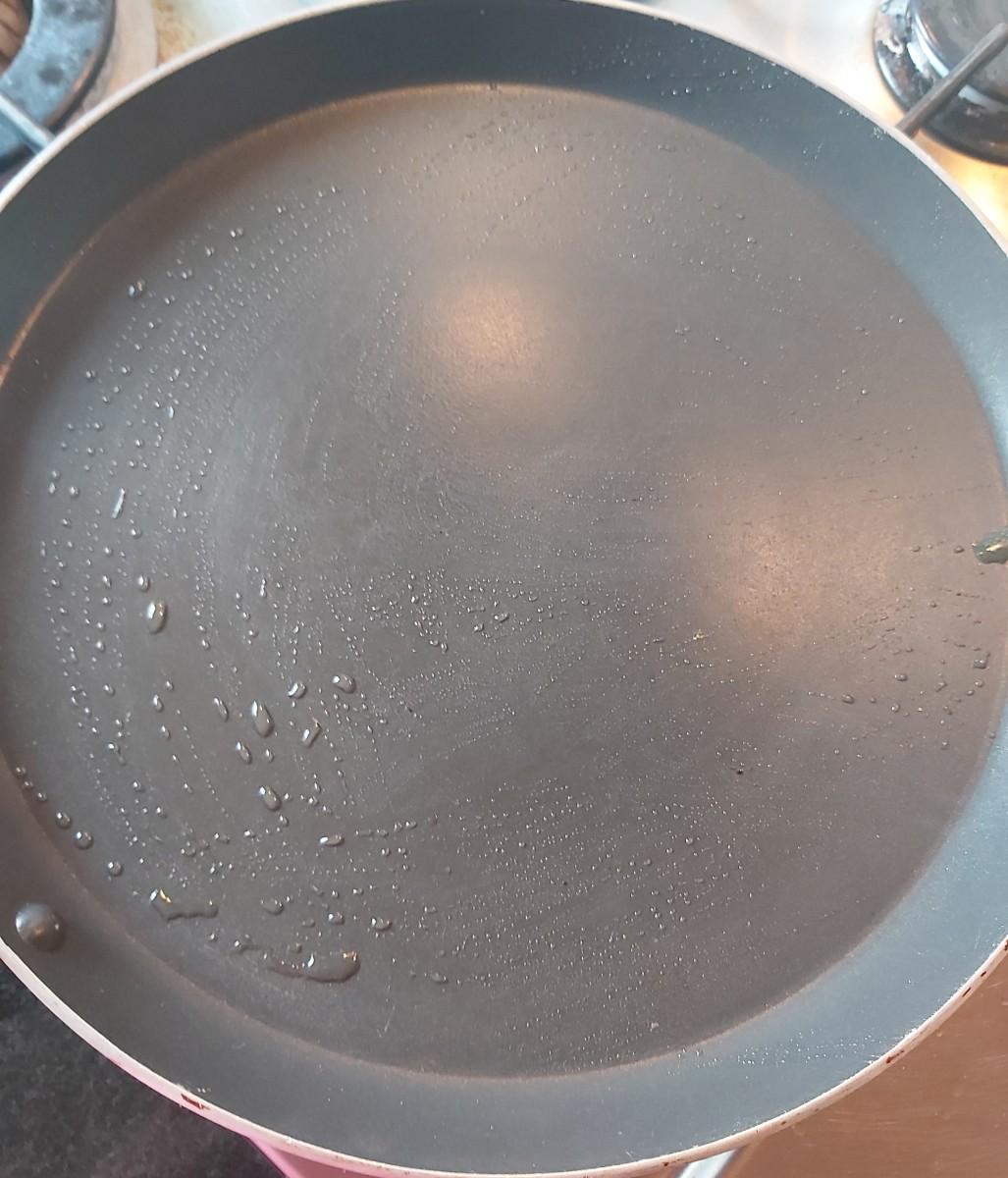 Heat tawa on low flame. Grease oil over tawa.