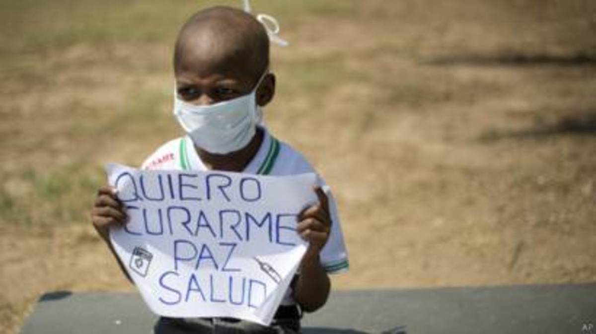 """Oliver Sanchez, a cancer patient from Venezuela. He and his family couldnt find the medicines needed for his treatment. He's holding a sign that reads """"I want to get better - Peace - Health"""" Oliver passed away due to the lack of essential treatments"""