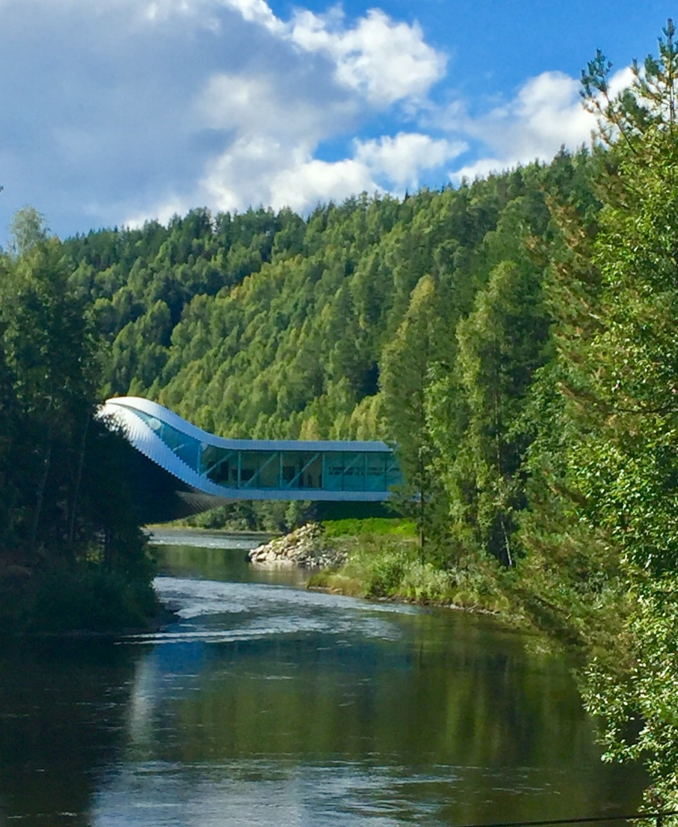The Danish architecture firm Bjarke Ingels Group's building twists and spans 60 meters across the Randselva river, where it makes a harmonious interplay with the area's beautiful woodland nature.