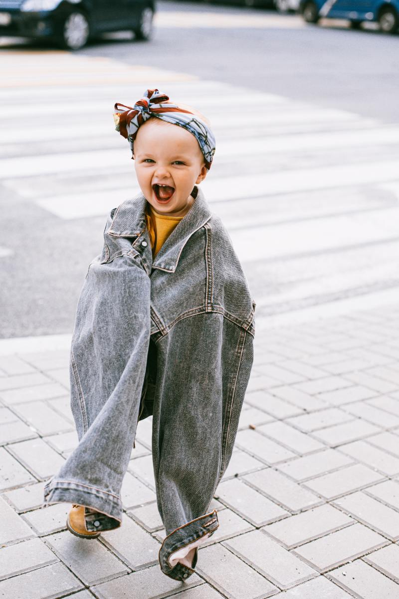 Smiling baby in an oversized jacket.