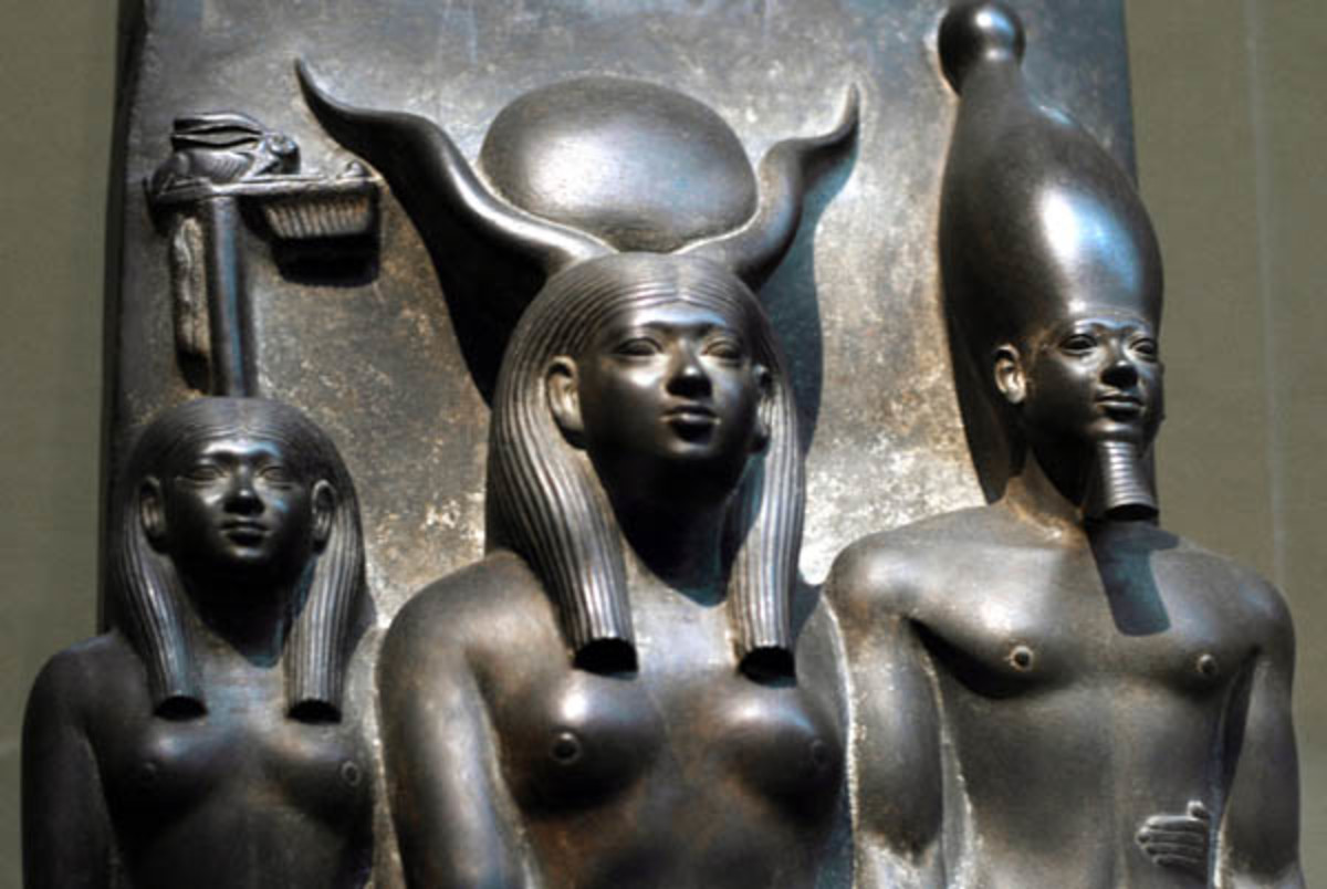 Men-Kau-Re stands on Hathor's left with his left foot advanced. His remarkably individualized facial feature - the prominent eyes, fleshy nose, moustache and protruding lower lip are all characteristics recognizable in other presentations of the King