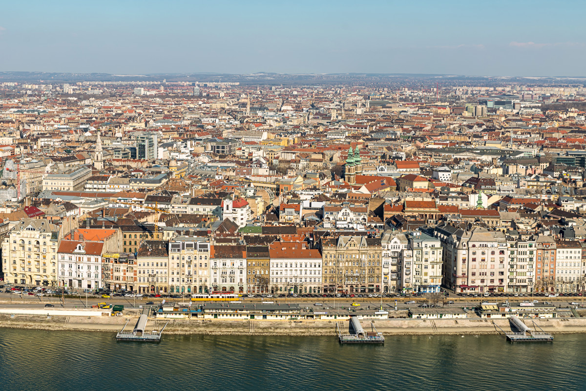 The landscape of Budapest. Budapest's total territory is 525 km² The city is divided into two parts by the Danube. The hilly left bank is called Buda, with over 20 hills within the territory of the capital, and the plain right bank is called Pest.