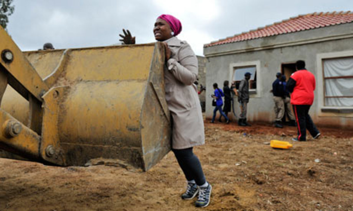 A South African woman unsuccessfully tries to prevent the demolition her home in Lenasia last week