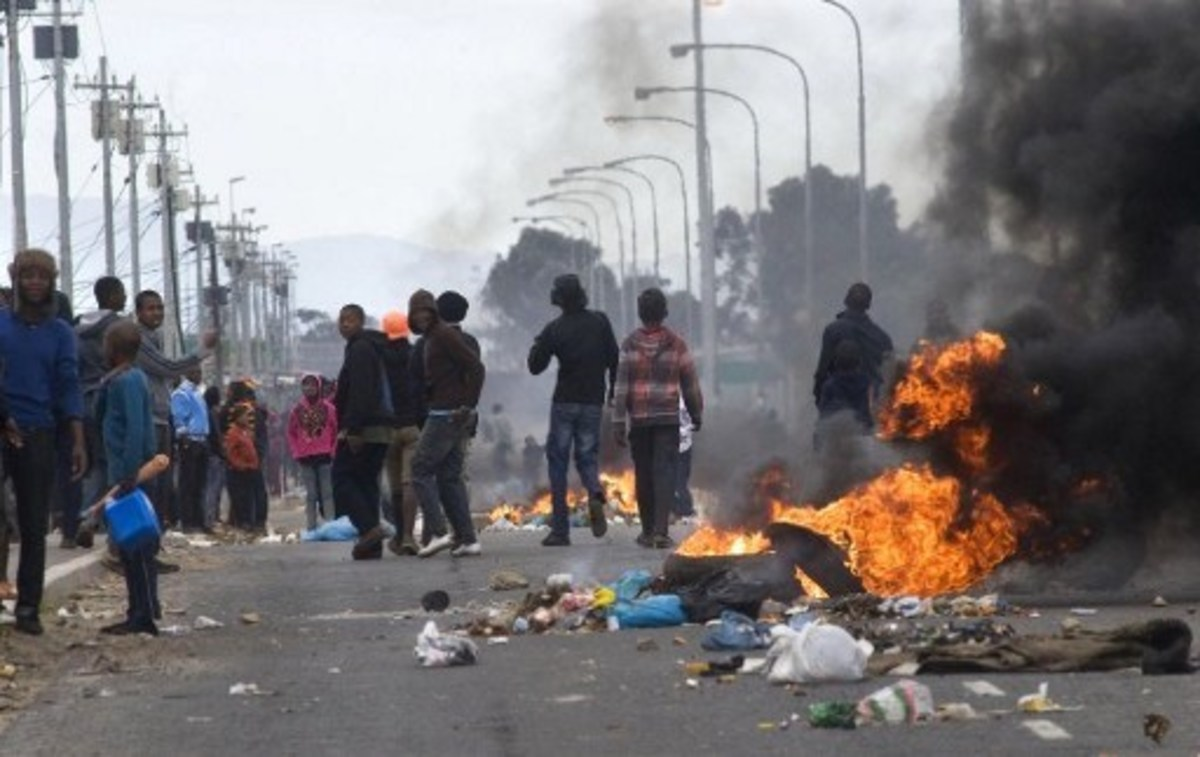 People walk past burning barricades during a protest against deficiencies in government services in Gugulethu, an impoverished township near Cape Town, in August 2012. - Protest in South Africa is on the rise and could lead to a fully-fledged revolt,