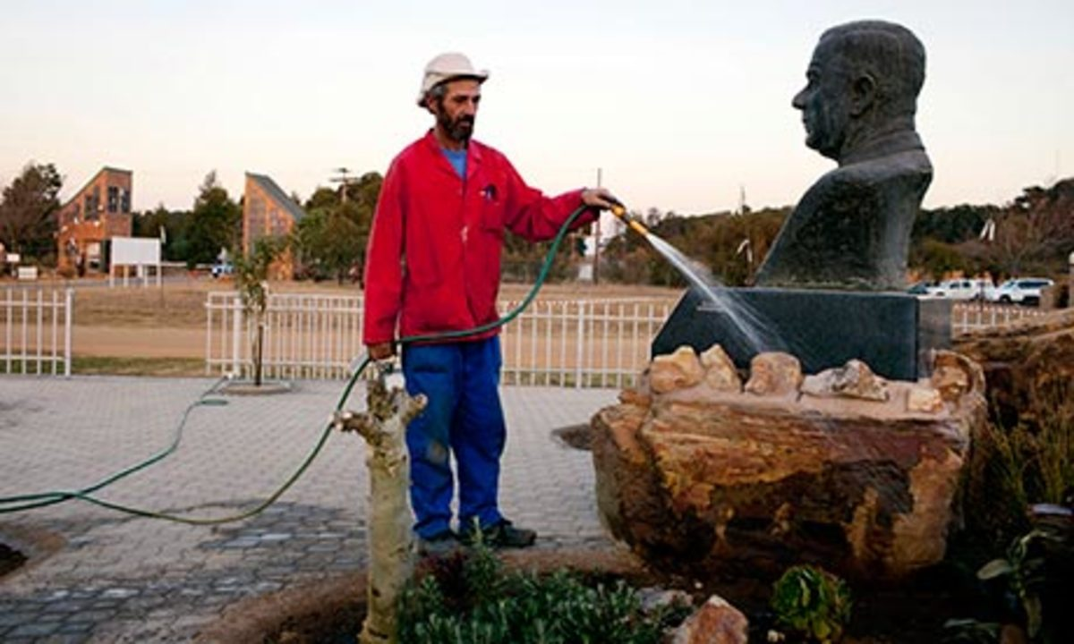 A municipality worker waters a monument to the former prime minister of South Africa Hendrik Verwoerd at the gate to Kleinfontein community, outside Pretoria, South Africa.