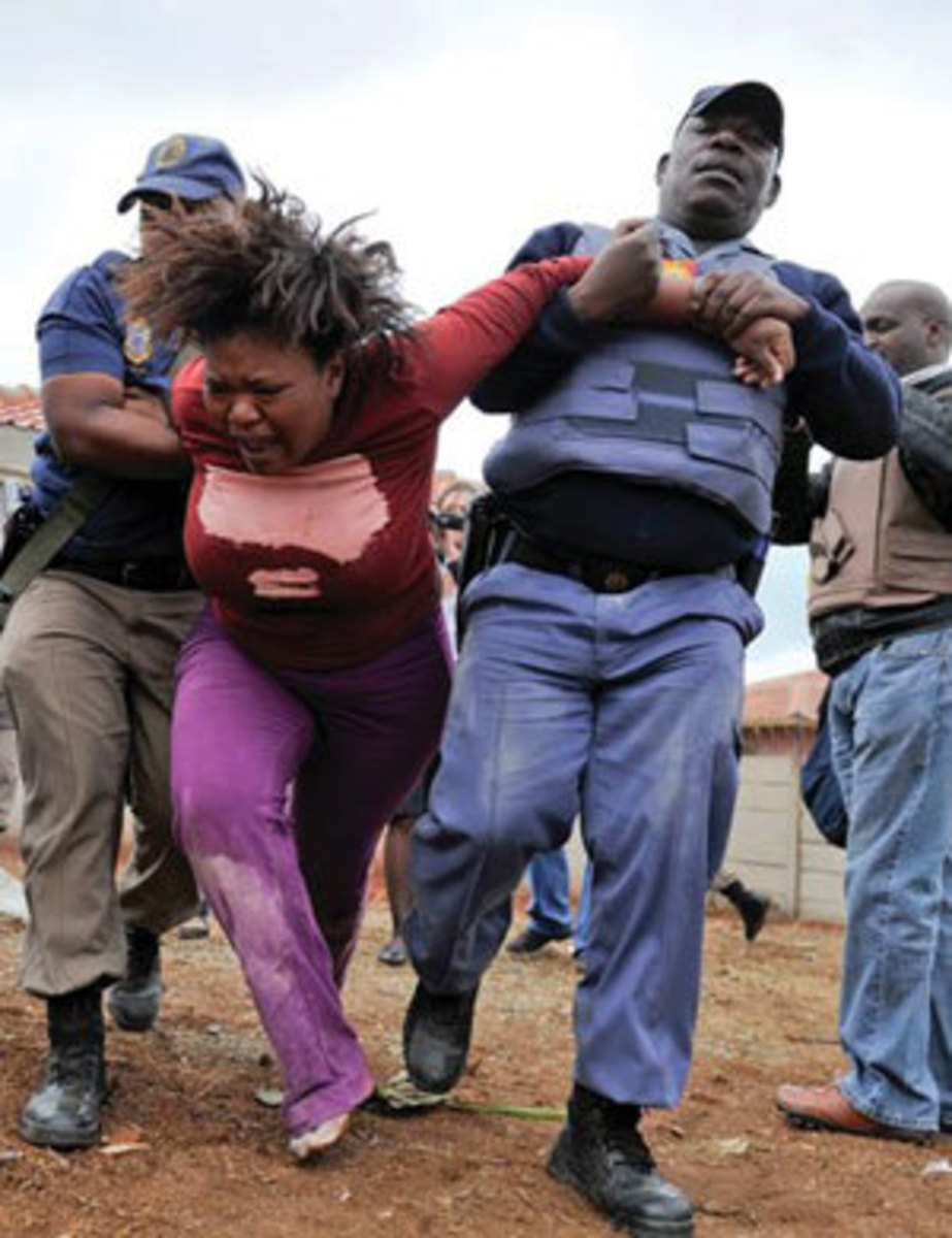 Police whisk away a Lenasia woman whose house was demolished.