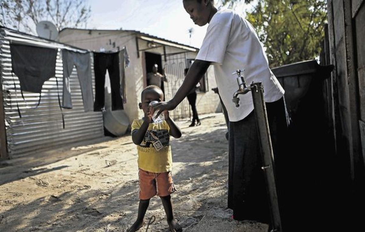 A woman gives her child water from a communal tap outside their home in Diepsloot
