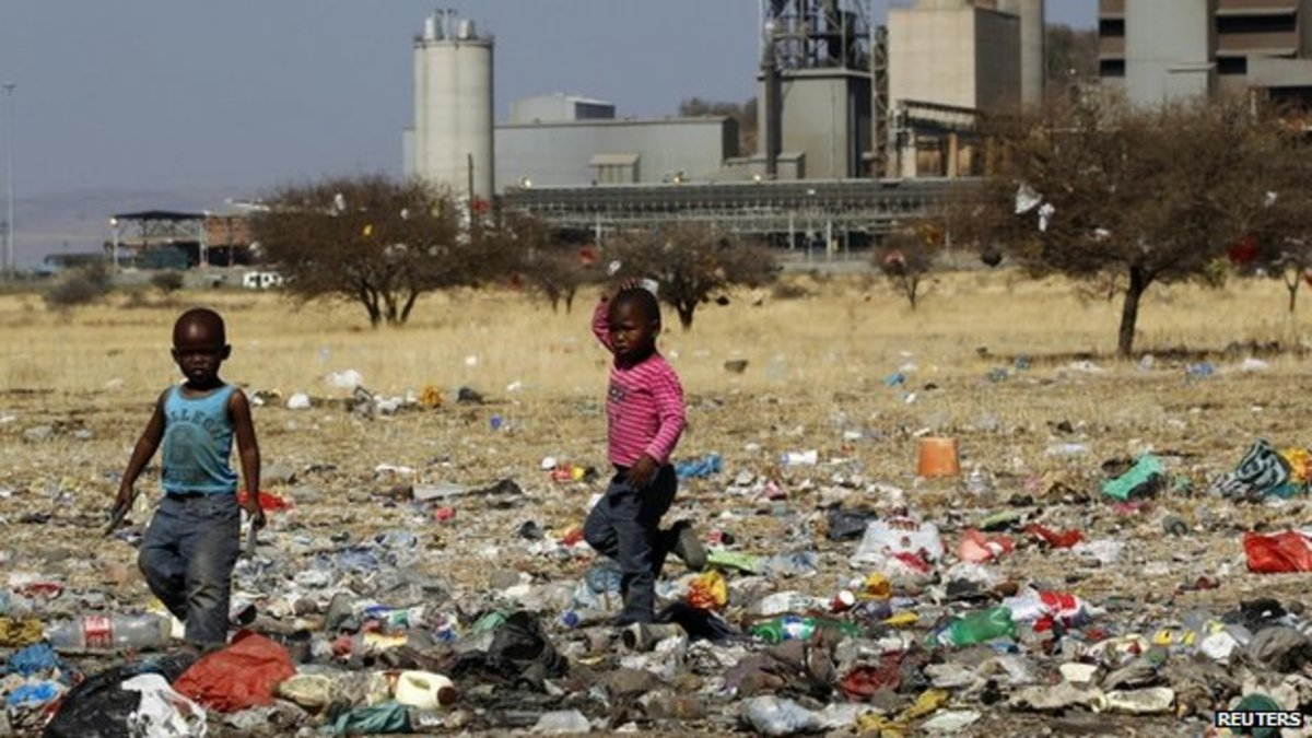 Children in South Africa foraging in the garbage dump lot
