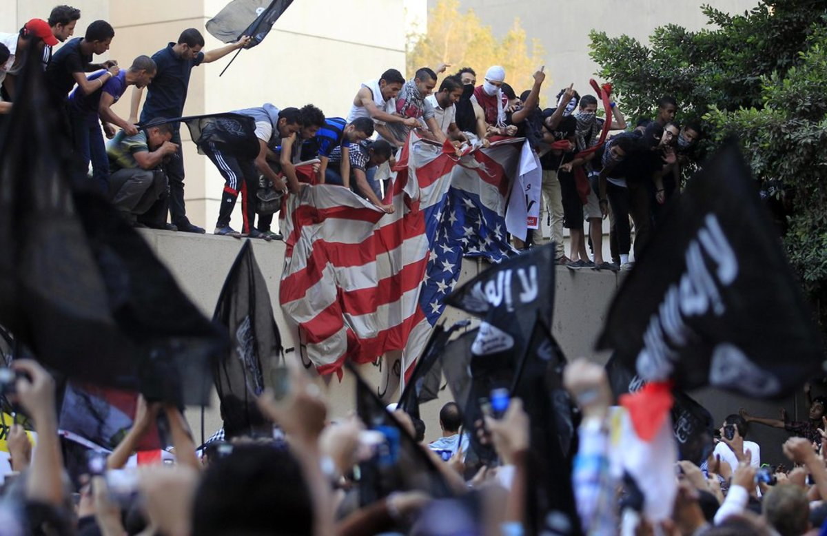 "Egyptian protesters tearing down the United States flag at the American Embassy in Cairo on Sept.11, 2012, during a demonstration against ""Innocence of Muslims,"" a video offensive to Islam."
