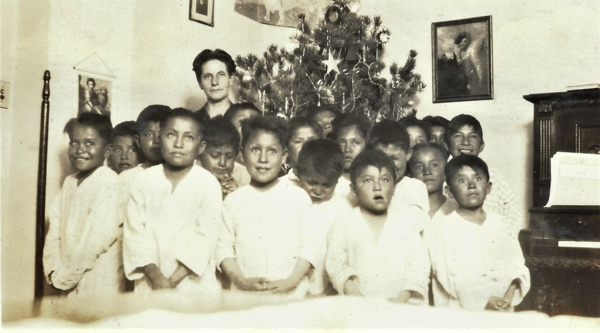 Navajo children and a teacher with the Christmas tree in the background.