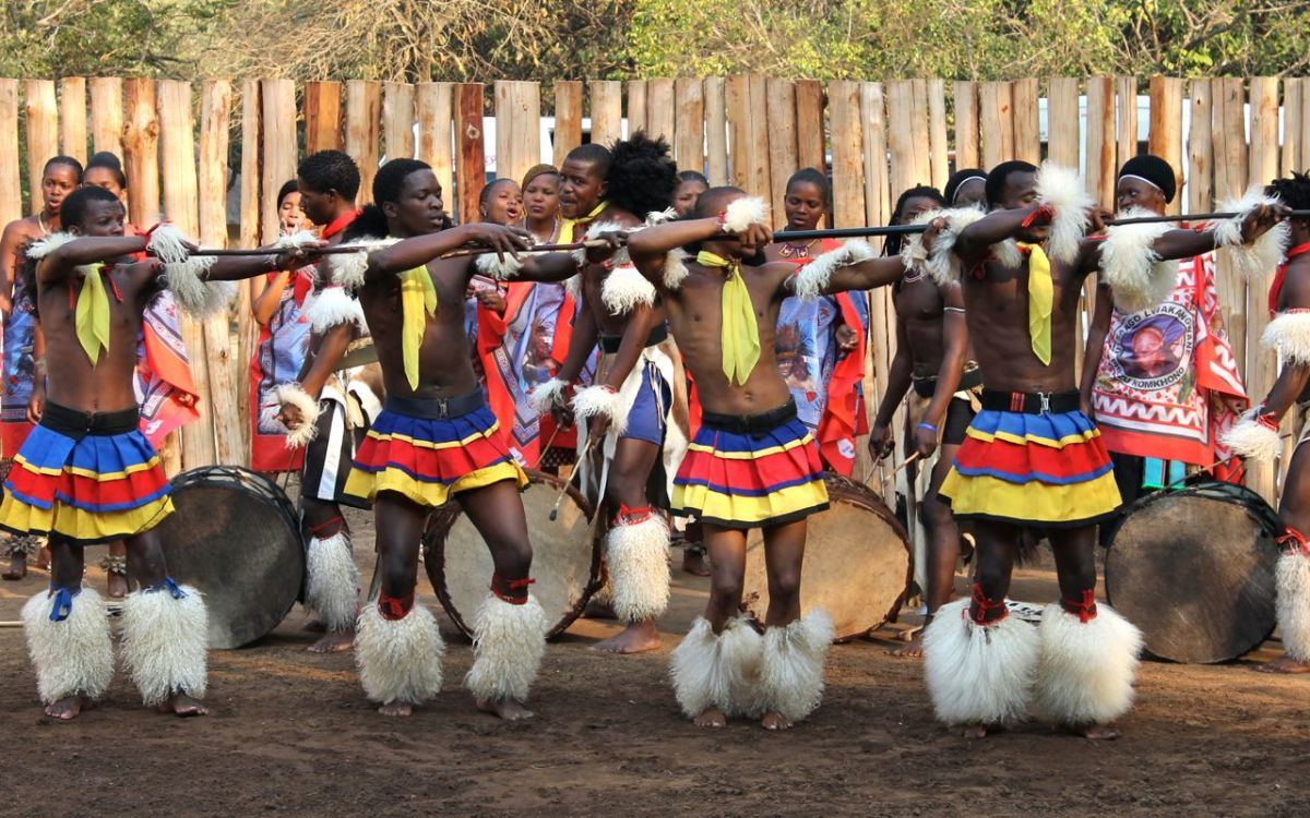 Swazi men doing their traditional dancing and singing, dressed in their cultural/traditional clothes