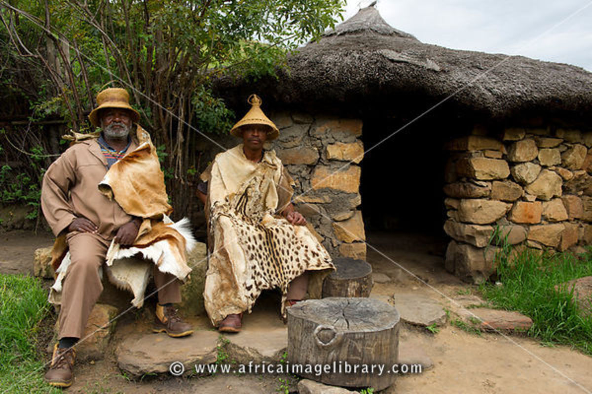 Two Basotho men sitted next to their house wearing anBasotho Blanket, Basotho Hats, and one is wearing an animal skin-next to their house...
