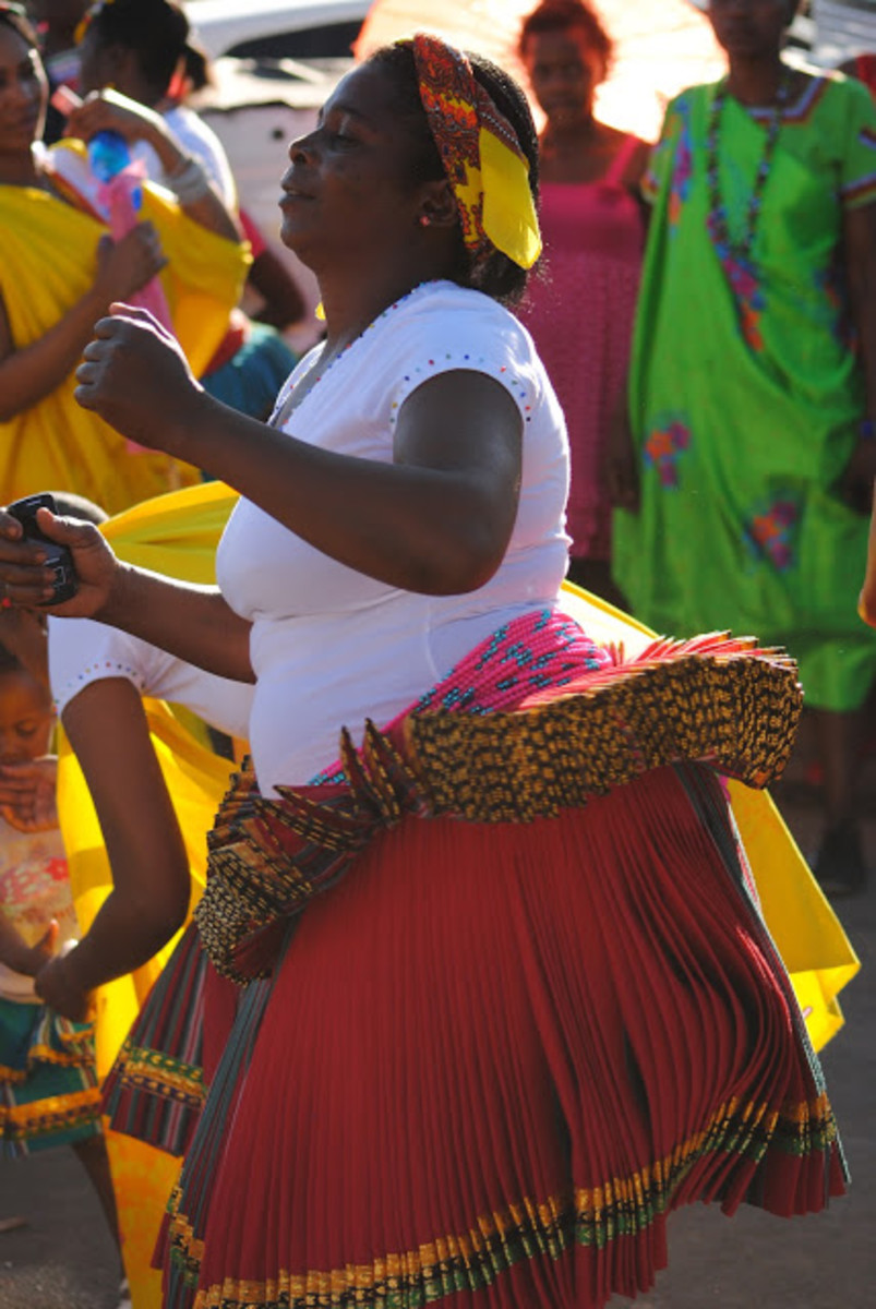 Tsonga woman dancing to trading beat in dance and wearing traditional Tsonga skirt